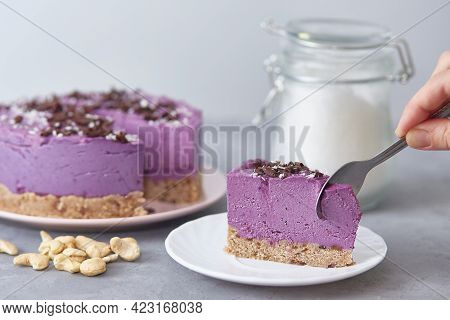 Vegan Raw Blueberry Cake. The Presence Of A Person Without A Face. The Hand With The Spoon Breaks Of