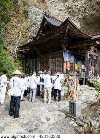 Kumakogen, Ehime Prefecture, Japan - April 10, 2018: O-henro Pilgrims Reading Sutras At Iwayaji, Tem