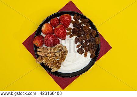 Plain Yogurt With Strawberries, Red Napkin, Raisins, Walnuts And Yellow Background