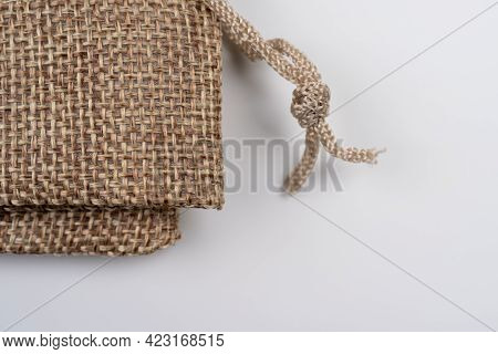 Linen Bags On White Background, Close Up Burlap Decorative Bag Tied With A Lace Of Rough Fabric Stud