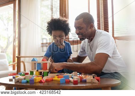 Brazilian Father And His Little Son Playing Building Tower From Wooden Block Toy On Sofa In Living R