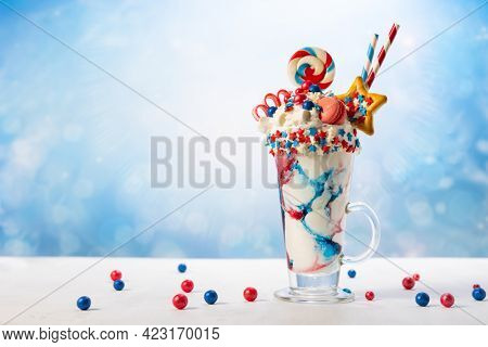Crazy milk shake with ice cream,whipped cream, marshmallow,cookies and colored candy in glass. Sweet dessert for Fourth of July. Idea milkshake for Patriotic day.