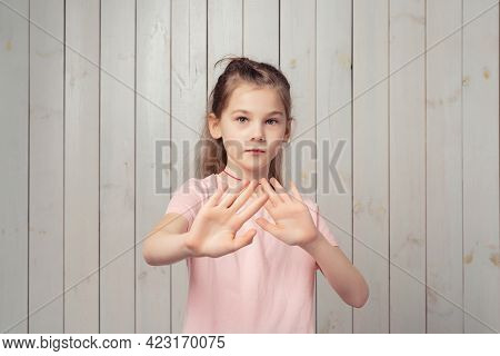 Portrait Of Scared Little Girl 9-11 Years Old Defending Herself From Something Frightening, Standing