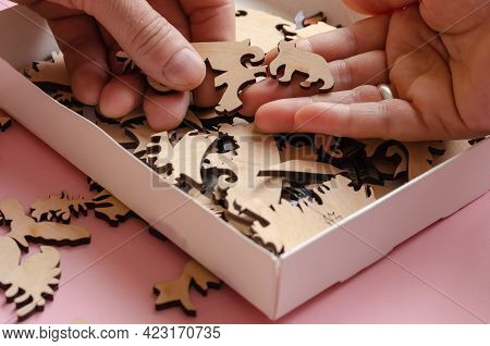 An Open Box With A Wooden Jigsaw Puzzle Close-up. Adult Man And Woman Choosing A Piece Of A Complica