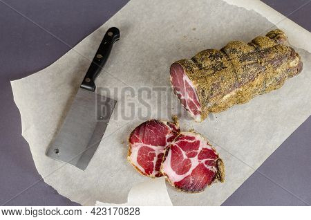 Cured Meat, Pork Neck, Coppa. A Piece Of Appetizing Air-dried Pork On Parchment. Ready-to-eat Food.