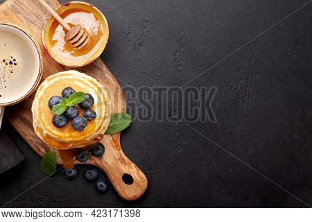 Healthy breakfast with pancakes. Homemade american pancakes with berries and honey. Top view flat lay with copy space