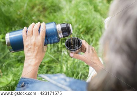 Senior Woman Camping In Nature. Close-up Of Female Hands Holding A Thermos And A Mug Outdoors. An El