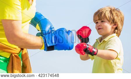 Father Is Training His Son Boxing. Little Boy Sportsman At Boxing Training With Coach. Little Boy Do