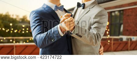 homosexuality, same-sex marriage and lgbt concept - close up of happy male gay couple holding hands and dancing on wedding over roof top party background