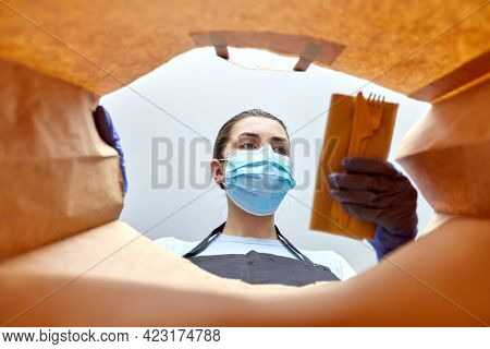 health protection, delivery and pandemic concept - saleswoman or female restaurant worker in protective medical gloves and mask packing takeaway food into paper bag