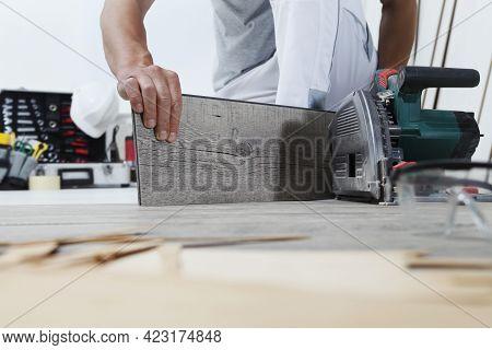Worker Hands Installing Timber Laminate Vinyl Floor. Wooden Floors House Renovation.