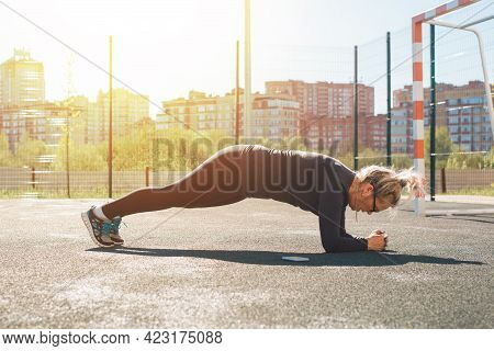 Adult Woman Practicing Plank Exercise Outdoors. Sportswoman Fitness Training On The Sports Ground On