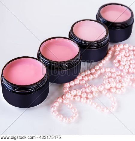Cosmetics For Hand Care. Color Coating For The Nail Plate In Black Doses And Pink Pearl Beads That E