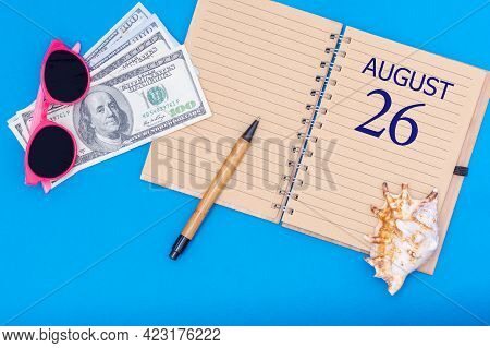 Travel Concept Flat Lay - Notepad With The Date Of 26 August Pen, Glasses, Dollars And Seashell On B