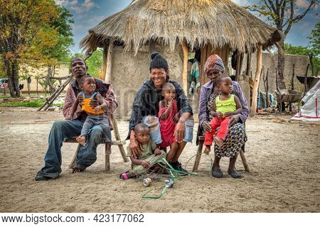 three generations extended African family in front of their thatched roof hut, village in Botswana