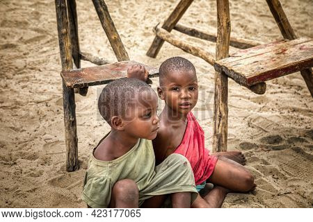 two African kids sited on the sand next to few traditional wooden chairs in a village in Botswana