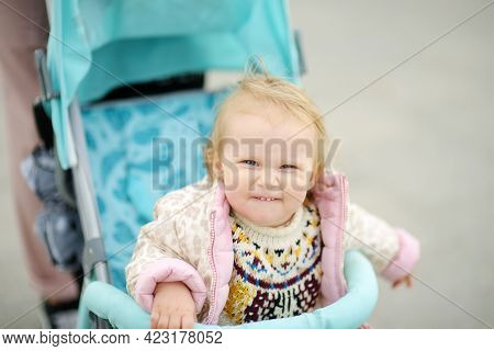 Funny Cute Toddler Girl Is Riding Into Baby Stroller During Stroll. Active Leisure And Walking For F