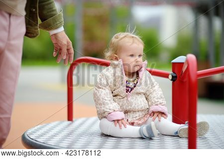 Toddler Girl Having Fun On Outdoor Playground. Young Father Rides Daughter On Carousel. Spring/summe