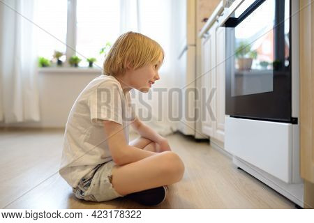 Glad Boy Sitting On The Floor Near Kitchen Stove And Waiting For A Pie Or Other Baked Goods To Be Pr