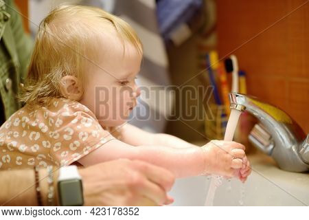 Cute Baby And Her Dad Washing Their Hands With Soap In Bathroom Together. Hygiene For Little Child.