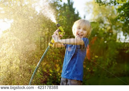 Funny Little Boy Watering Plants And Playing With Garden Hose With Sprinkler In Sunny Backyard. Pres