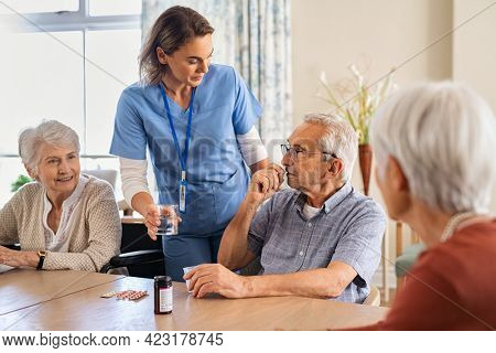 Nurse giving medicine to group of seniors at nursing home. Caregiver giving medicine to old patient sitting at table at care facility centre. Elderly man taking pills from healthcare worker.