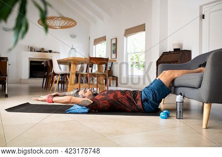 Mature mixed race man doing press on a yoga mat while keeping legs on sofa at home. Mid adult indian man practicing crunches during morning routine. Fit middle eastern guy doing abs exercise at home.