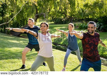 Mature multiethnic couple doing sport and physical exercises outdoor with friends. Group of active mature man and beautiful mid adult women doing workout at park in the afternoon.