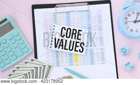 Notebook With Text Inside Core Values On Table With Calculator And Some Sheet Of Papers With Charts