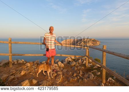 Man with dog in front of landscape with Les Medes islands in sunset at the horizon
