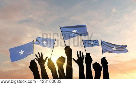 Silhouette Of Arms Raised Waving A Somalia Flag With Pride. 3d Rendering