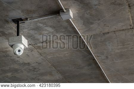 Modern Surveillance Cameras For Ceiling Mounted On Concrete Wall In The Parking Lot. The Concept Of