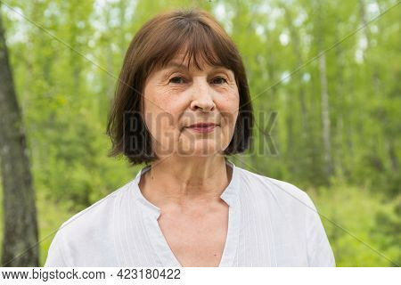 Portrait Of One Woman 60 Years Old In A Summer Forest.