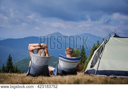 Rear View Of Tourists Pair Basking In The Sun, Sitting In Trekking Chairs Near Tent In Their Campsit