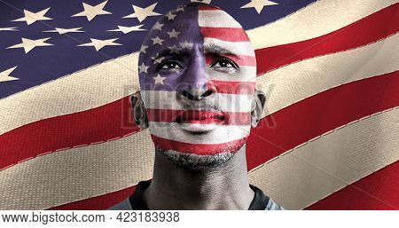 American flag over face of african american male athlete against american flag. american patriotism and sports concept