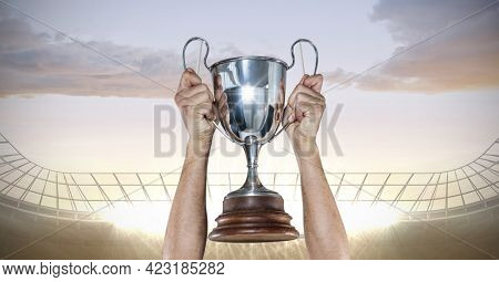 Mid section of caucasian male athlete lifting a trophy against floodlights in background. sports and fitness concept
