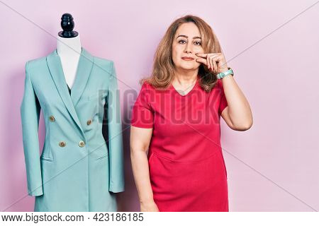 Middle age caucasian woman standing by manikin mouth and lips shut as zip with fingers. secret and silent, taboo talking