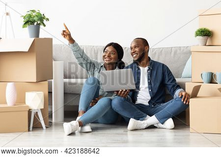 Smiling African Spouses Sitting With Laptop In New Flat And Pointing Away