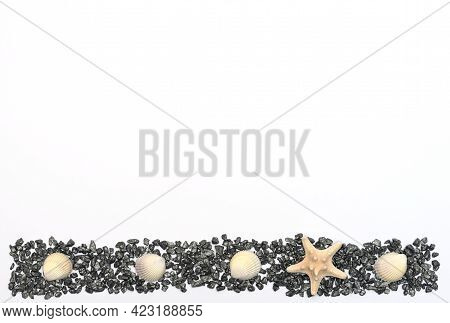 White Starfish On Small Dark Stones With Sea Shells On White Background. Summer Time, Minimalism Con