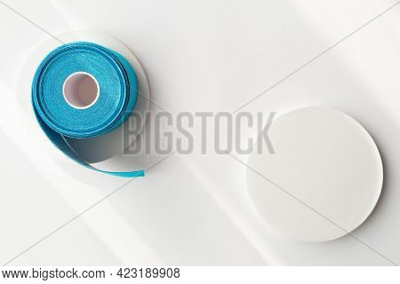 Blue Roll Of Kinesiology Tape On White Background With Shadows And Podiums, Flat Lay. Recovery, Anti