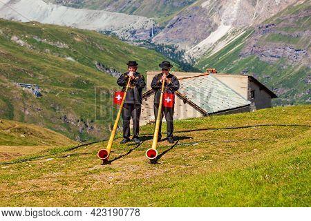 Zermatt, Switzerland - July 16, 2019: Swiss Alphorn Blowers Are Playing Music Near The Matterhorn Mo