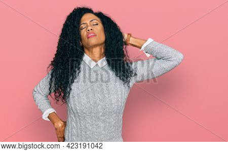 Middle age african american woman wearing casual clothes suffering of neck ache injury, touching neck with hand, muscular pain
