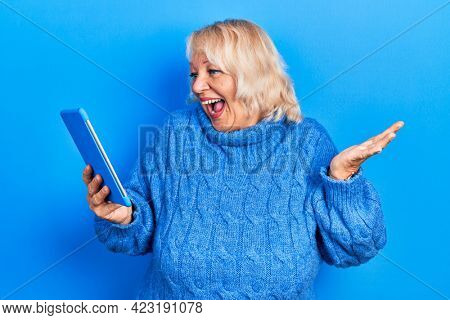 Middle age blonde woman using touchpad device celebrating victory with happy smile and winner expression with raised hands