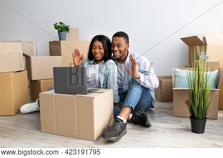 Young Black Family Chatting Online Via Laptop, Sitting Among Carton Boxes In New Apartment And Wavin