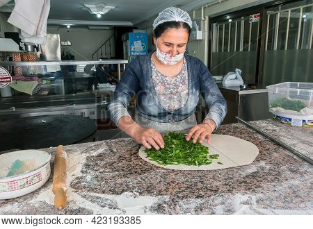Izmir, Turkey: Woman Cook Cooking Turkish Gozleme With Dough And Herbs Inside Small Traditional Cafe