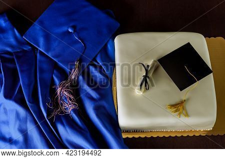 Top View Of Blue Graduation Gown And Cap With Cake For End Of School.