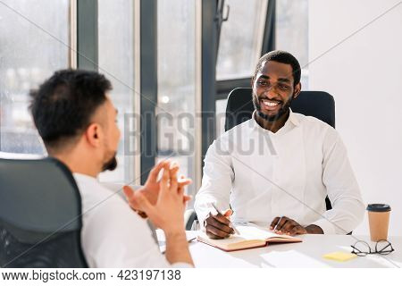 Business Colleagues Talking While Sitting At The Table In The Office