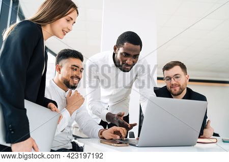 Group Of Multiracial White Collar Workers In The Office Behind A Laptop