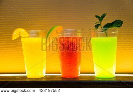 Glasses With Air Bubbles In The Background Light Of A Yellow Lemonade With A Slice Of Lemon, A Red D