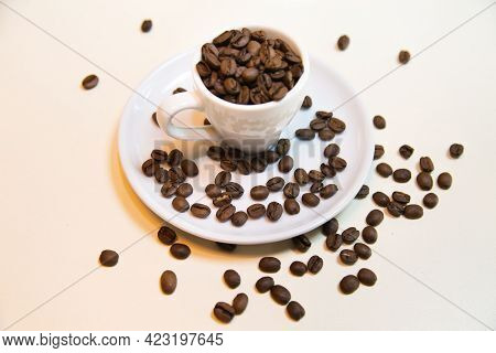 White Cup On Saucer Filled With Brown Coffee Beans On A White Background. Confectionery Products Dri